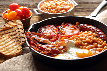English Breakfast with sausages, grilled tomatoes, egg, bacon, beans and bread on frying pan.
