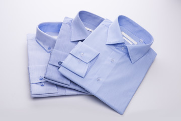 Three blue men's shirts folded in a pack on a white background.