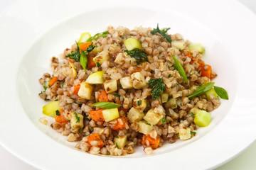 Juicy buckwheat porridge with vegetables and herbs in deep plate