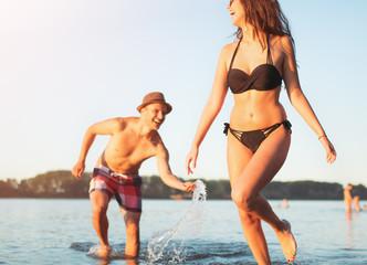 Happy couple runs through waves on sunlit beach, splashing the water in the sea.