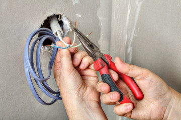 Electricians clears the ends of wires using pliers, hands close-up.