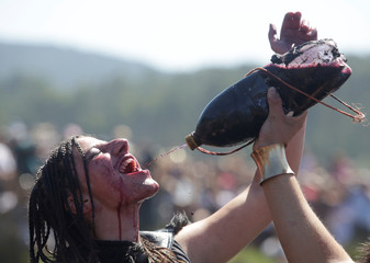 A woman dressed up as a Viking drinks local red wine during the annual Viking festival of Catoira in north-western Spain