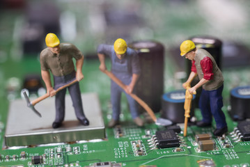 Miniature Workers On Top Of A Circuit Board