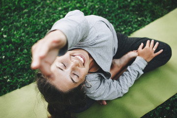 Cheerful and happiness young woman practicing yoga on the green lawn outdoors. Calmness and relax, female happiness
