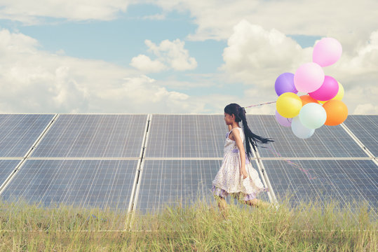 A funny girl carrying a colorful balloon running in a meadow with a Solar panel, photovoltaic. Concept of Eco-Friendly ,Clean Energy , Pure energy and Sustainable energy