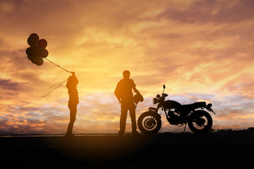 Silhouette of Couple standing with a motorbike in the sunset, women holding balloons, Happiness and joy dating couples.