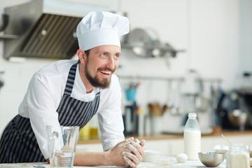 Cheerful baker or pastry-chef leaning at his workplace with ingredients for dough
