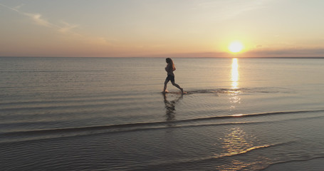 Aerial shot over teen girl barefoot running in water on baltic sea beach in sunset time