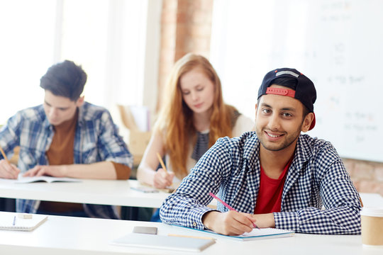 Clever teenage learner sitting by desk during exam and carrying out written task or writing essay
