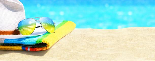 Sonnenbrille, Hut und Handtuch am Strand
