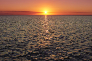 Deep sunset over calm smooth sea with bright colors and plenty of copy space. Beautiful natural summer seascape. Image of sunset with yellow red gradient colors. Horizontal photo. Red purple sunset