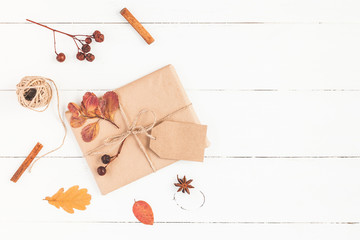 Autumn composition. Gift, autumn leaves, cinnamon sticks, anise star on wooden white background. Flat lay, top view, copy space