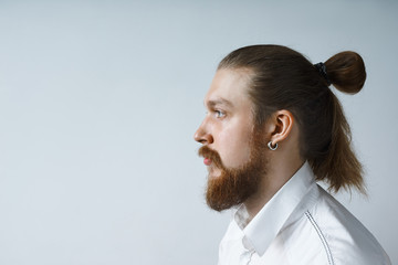 Side view portrait of serious stylish young bearded manager wearing his long red hair in knot looking ahead of him at blank copyspace wall for your promotional content, having thoughtful look