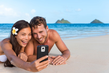 Wall Mural - Beach vacation couple taking fun phone selfie on Hawaii vacation. Asian girl Caucasian man relaxing on Lanikai beach, Oahu, on summer holidays using smartphone for pictures together.