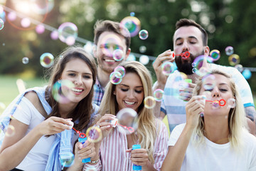 Happy group of friends blowing bubbles outdoors