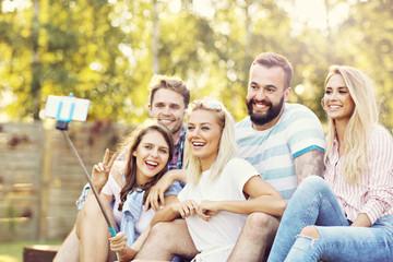 Happy group of friends taking selfie outdoors
