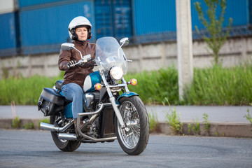 Side view at the moving motorcycle with women motorcyclist, chrome chopper driving on road