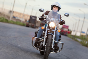 Front view at the moving motorcycle with young women motorcyclist, chrome chopper driving on road