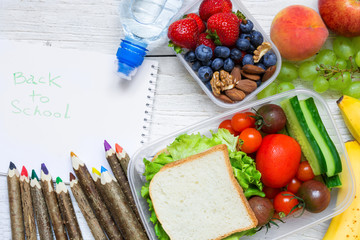 school lunch boxes with sandwich, fruits, vegetables and bottle of water with colored pencils and back to school inscription