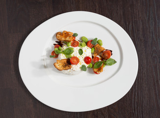 Delicious tomato and mozzarella cheese salad caprese, served on a white plate, with basil, croutons and balsamic vinegar.