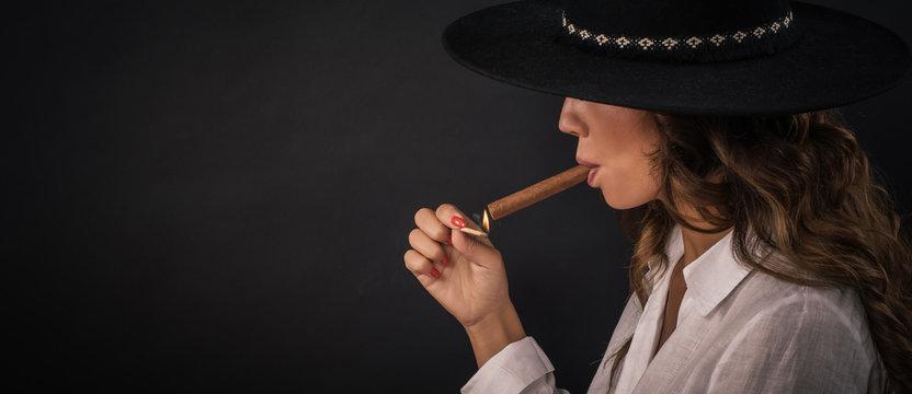 Portrait of sexy elegant lady woman with hat smoking cigar