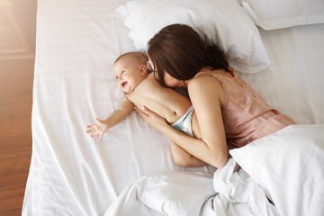 Young beautiful mom and newborn baby lying in bed smiling fooling at home. From above.