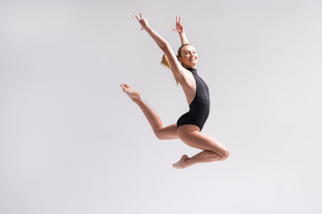 Foto op Aluminium Gymnastiek Joyful young woman practicing rhythmic gymnastics workout