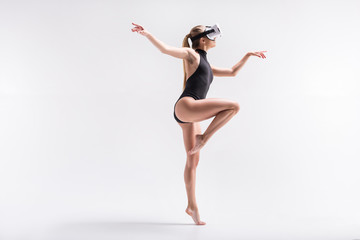 Pensive youthful girl dancing in goggles