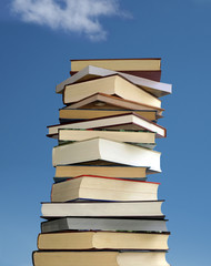 Stack of books on blue sky background