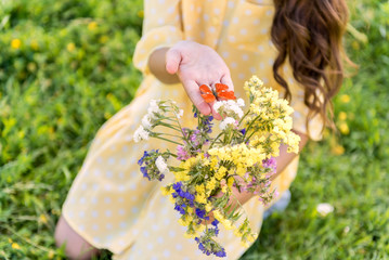 Pretty female child holding little moth near flowers