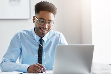 Happy businessman wearing elegant eyewear and shirt watching video online while sitting in front of opened laptop in earphones. Dark-skinned male communicating online with his friends, smiling gently