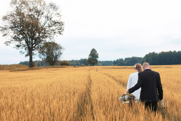 Just married lovers walking in a field in autumn day