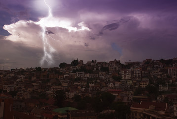 Tropical storm, thunderstorm, rain. Lightning above the city in the night violet sky