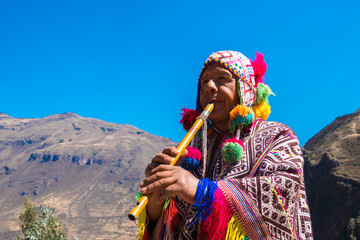 Peruvian man playing a flute, Sacred Valley, Cusco, Peru