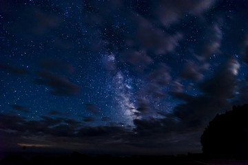 Night sky full of stars glittering through parting clouds on a dark night in the wilderness