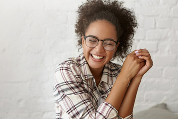 Positive emotions and happiness concept. Pretty young woman with dark skin wearing eyeglasses and casual clothes closing her eyes with enjoyment while recieving compliment from handsome boy.