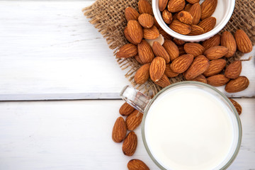 Close up top view of healthy almond milk in the drinking glass with seed in white cup and wooden spoon on white wooden table plate with copy space
