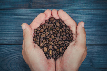 Blue wooden table and hands holding coffee seeds.