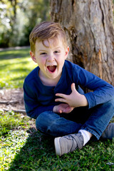 Excited young boy sitting crossed legged against tree trunk in park