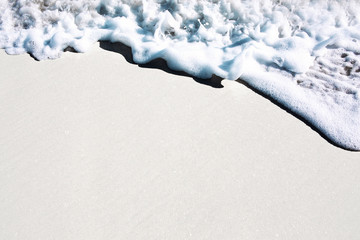 Sea foam on beach shoreline