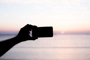 silhouette hand holding smartphone take photo at sunset.