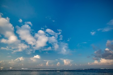 Morning seaview of shoreline with white waves in ocean. Beautiful clouds on the sky over the sea