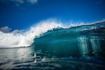 Front view of Big ocean wave in daylight. Blue sky with clouds. Sea Water surface for surfing sport activity. Nobody on picture. Vibrant bright tropical colorful image.