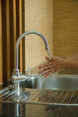 Woman Washing Her Hands At Sink