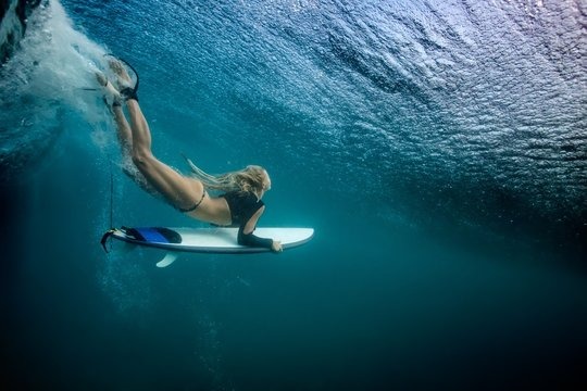 Blonde girl Surfer holding white surf board Diving Duckdive under Big Beautiful Ocean Wave. Turbulent tube with air bubbles and tracks after sea wave crashing.