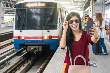 Asian woman passenger with casual suit taking selfie by the smart mobile phone in the BTS Skytrain rails or MRT subway for travel in the big city, lifestyle and transportation concept
