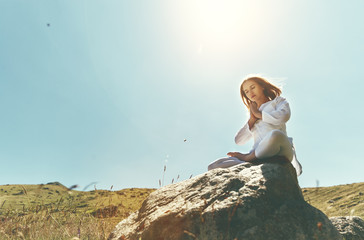 Fototapete - woman practices yoga and meditates in   lotus position on mountains, peak
