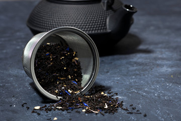 black cast iron kettle and dry tea, closeup