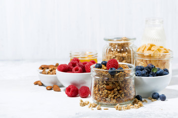 healthy products for breakfast, granola and fresh berries on white table
