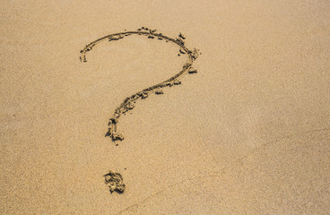 question mark drawn on the sand of a beach in summer